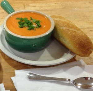 Carrot Ginger soup served with green onions on top and a mini baguette